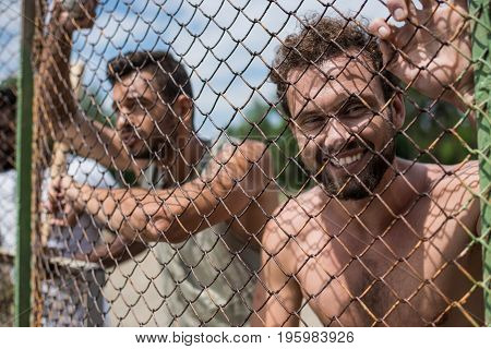 group of young men leaning on fence during baseball game