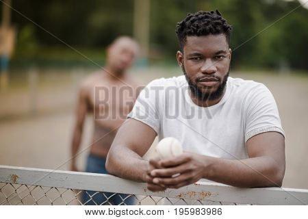 Young Handsome African American Man With Baseball Ball Leaning On Fence On Court