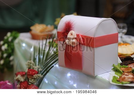A white box with red satin bow stands on the table.