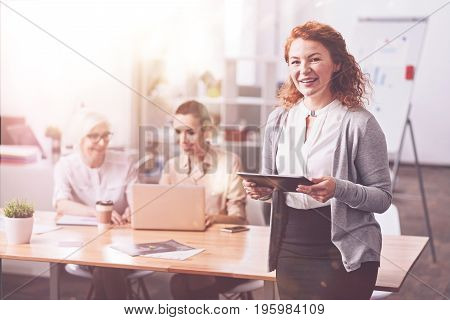 Skillful professional. Talented energetic positive lady looking delighted while holding a tablet and spending a productive day in the office