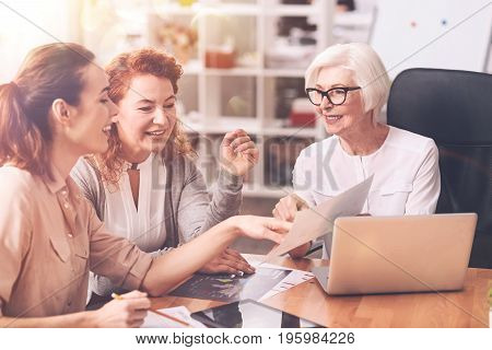 Tell me more about this. Admirable charismatic senior woman showing a diagram to her colleagues telling them explaining it to her