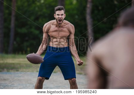 young handsome male football player yelling and holding ball on court
