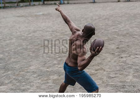 Young Handsome African American Male Football Player With Ball On Court