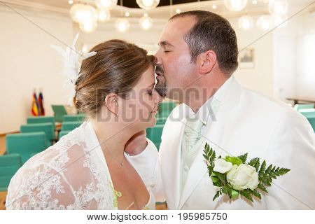 Blond Bride Kisses A Groom In A City Hall