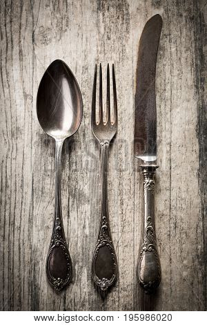 Old antique spoon fork and knife on dark wooden background.