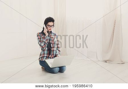 Relax with computer. Girl with laptop. Young female in glasses sitting on floor with laptop, talking on mobile, cell phone. Hipster student, freelancer woman at home.