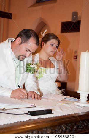 Bride And Groom Signing The Register After The Ceremony