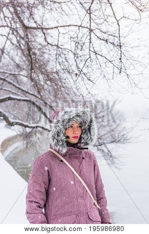 Young Woman In Winter Coat Walking Along Tidal Basin Path During Snow Storm In Washington Dc