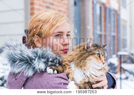 Young woman holding maine coon cat with green eyes outside in snow
