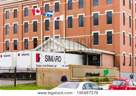 Montreal Canada - May 26 2017: Simard truck parking lot garage in Quebec region city with JTI Macdonald sign