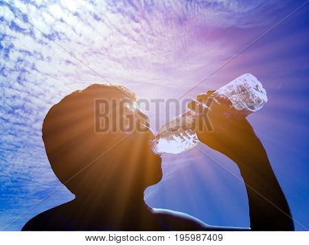 The sun shines on a clear day. It makes the weather very hot.A man was so thirsty because he ran for a long time. He is drinking bottled water. poster