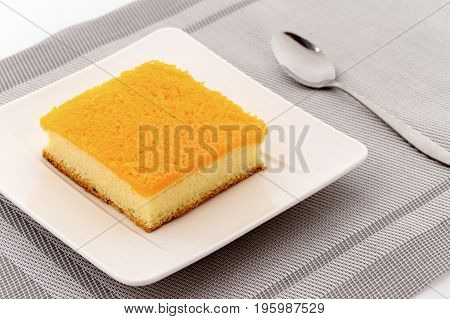 Golden egg strips topping on butter cake or Foi Thong cake on plate with spoon