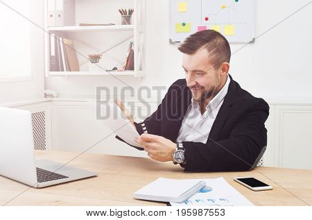 Young concentrated on papers businessman with laptop in modern white office interior. Handsome serious man employee at work reading documents. Lifestyle portrait