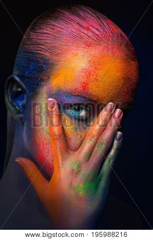 Holi colours festival. Portrait of model with colorful makeup posing on dark studio background. Abstract art make-up, crop