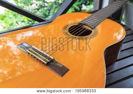 A classic guitar on wooden table with tree background.