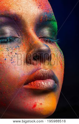 Holi festival of colors background. Female face art with creative make up. Closeup cropped studio portrait of young fashion model with bright body art