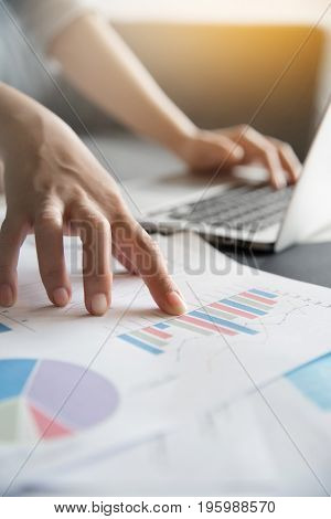 Close up of Business woman hands on Graph financial diagram documents.