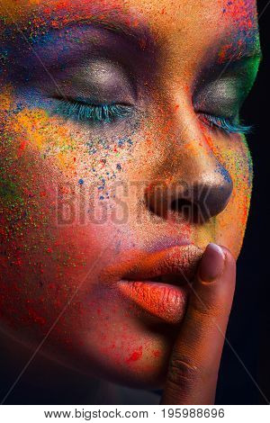 Fashion model with colorful make up show hush sign on dark studio background. Beautiful woman with creative splash makeup, crop
