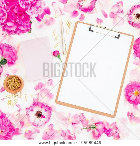 Blogger of freelancer composition. Workspace with clipboard, notebook, pen and pink roses on white background. Flat lay, top view.