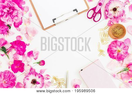Stylish workspace with clipboard, notebook, pink flowers with petals and accessories on white background. Flat lay, top view.