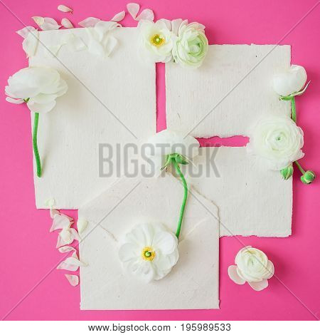 White flowers with petals and vintage paper envelope and cards on pink background. Flat lay, top view. Retro background.