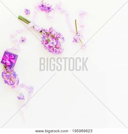Bouquet of pink flowers and ring box with shabby tapes on white background. Flat lay, top view.
