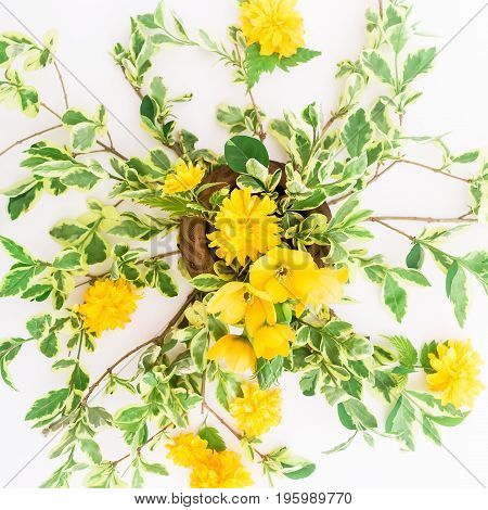 Floral pattern made of branches with yellow flowers and leaves on white background. Flat lay, top view. Floral background.