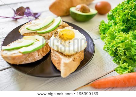 Sandwich with avocado and egg on white table. Fitness breakfast