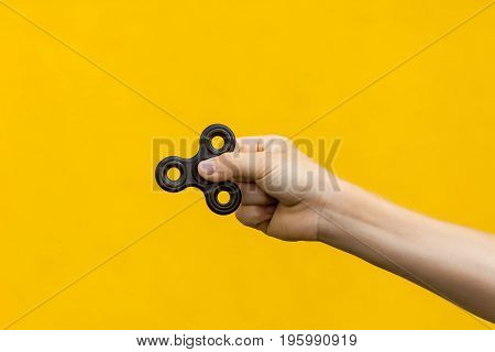 human hand holding black fidget spinner on yellow background.