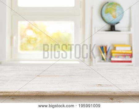 Wooden table with blurred background of kids room and window