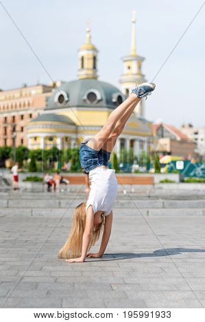 Active kid girl gymnast stretching and doing splits on the street. Young girl acrobat. The girl is engaged in gymnastics