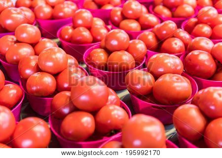 Closeup Of Red Ripe Tomatoes In Baskets At Farmers Market
