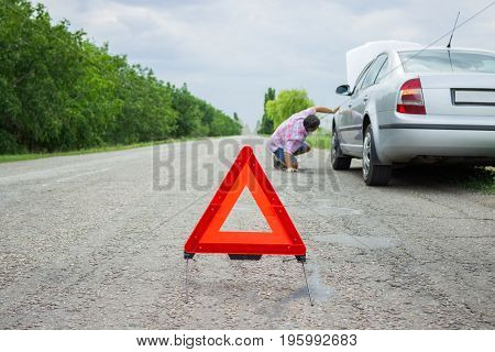 road sign emergency and traffic concept - warning triangle over broken car