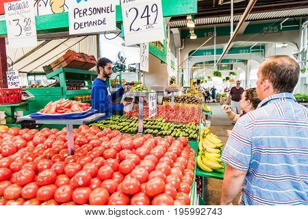Montreal Canada - May 27 2017: Man buying produce by tomato stand with sample slices at Jean-Talon farmers market with fruit displays