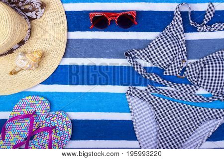 swimsuit with beach accessories on blue background. Sun Glasses Top View Seashell Shorts Flip flops Swimsuit