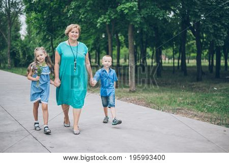 Grandmother playing in the park with grandchildren, siter with brother