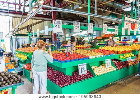 Montreal Canada - May 27 2017: Man selling produce by fruit stand with woman buying strawberries at Jean-Talon farmers market with displays