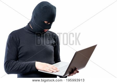 A Hacker In Black Clothes And A Mask With A Laptop On A White Background