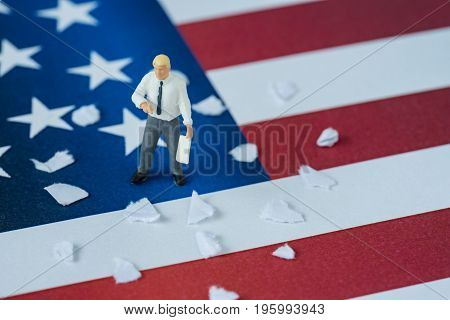 miniature people american businessman holding document with tear paper trash standing on United State national flag.