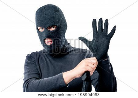 Portrait Of A Robber In A Mask On His Face Straightens A Glove On A White Background