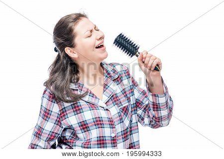 Emotional Girl In Pajamas Singing In Hairbrush On White Background
