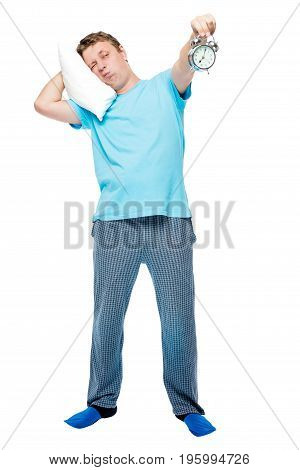 Cute Man In Pajamas Holds An Alarm Clock In The Early Morning On A White Background