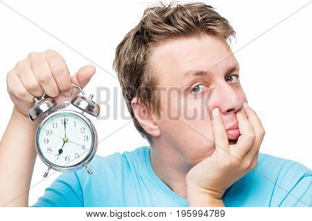 Close-up Portrait Of An Unwanted Man In The Morning With An Alarm Clock On White Background