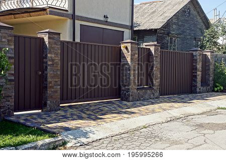 Gray brown iron fence in front of an asphalt road