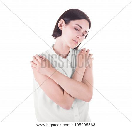 An unsatisfied pretty female standing isolated over the white background. A beautiful sad girl hugging herself. A young lady in a white blouse and short black hair.