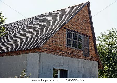 Fragment of a rural brick house with an attic and windows