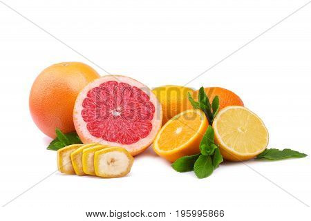 Various citrus fruits, isolated on a white background. Sweet tropical banana, ripe grapefruits, juicy oranges with green leaves. Summer fruits. Whole and cut healthy citrus fruits.