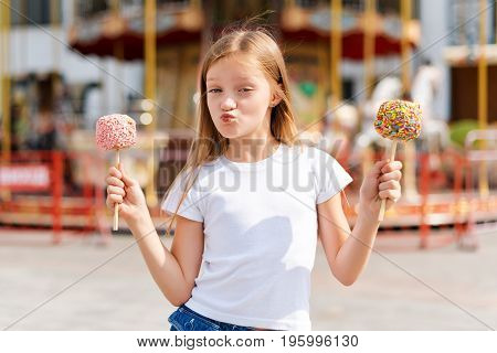 Cute little girl eating candy apple at fair in amusement park