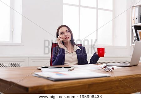 Business consulting. Young serious businesswoman talking by phone at modern office workplace, copy space