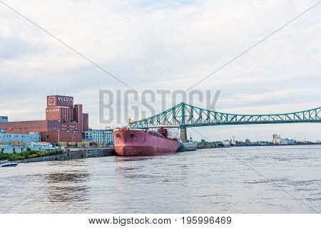 Montreal, Canada - May 27, 2017: View Of Old Port Area With Large Red Ship And Molson Factory In Cit